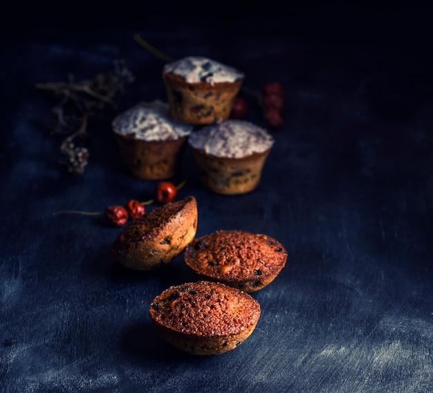 Queques redondos cozidos com uma mesa de madeira preta raisin, close-up Foto Premium