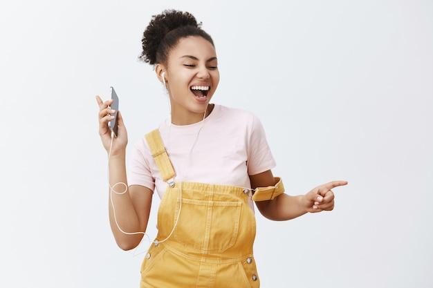 Quer dançar com alguém. retrato de uma mulher afro-americana atraente feliz e alegre em um macacão amarelo elegante, movendo-se no ritmo da música, ouvindo músicas em fones de ouvido, segurando o celular Foto gratuita
