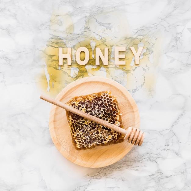 Querida palavra sobre o favo de mel com dipper na placa de madeira Foto gratuita