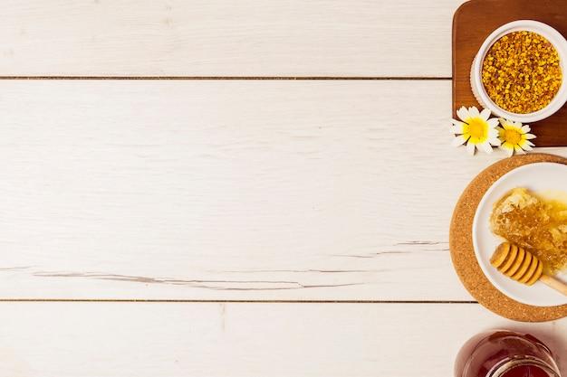 Querida; pólen de abelha e favo de mel, dispostos em linha sobre a mesa de madeira Foto gratuita