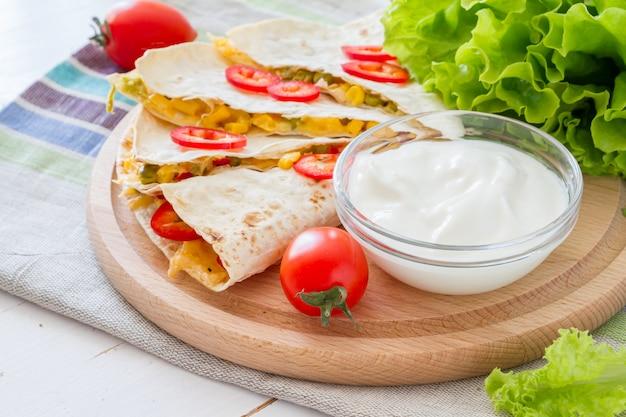 Quesadilla com creme azedo, salada e tomate Foto Premium