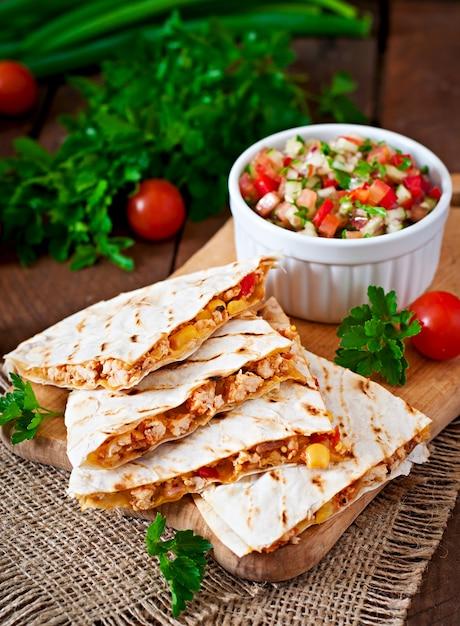 Quesadilla mexicana com frango, milho e pimentão e salsa Foto gratuita