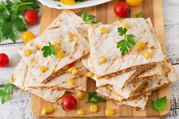 Quesadilla mexicano enrole com frango, milho e pimentão e salada fresca. Foto Premium