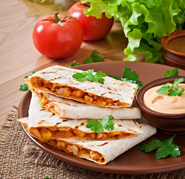 Quesadilla mexicano fatiado com legumes e molhos em cima da mesa Foto Premium