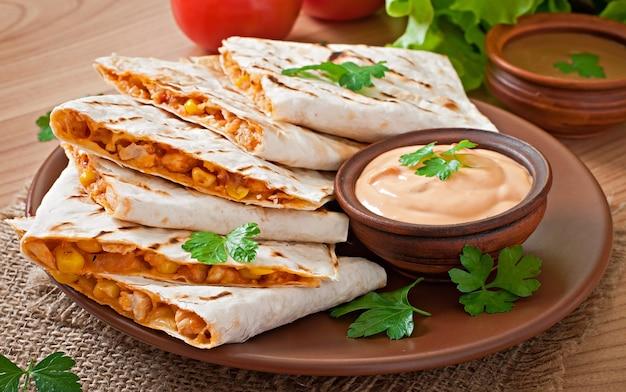 Quesadilla mexicano fatiado com legumes e molhos em cima da mesa Foto gratuita
