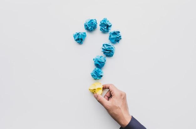 Questionar ou pensar conceitos de ideias com uma mão masculina segurando uma bola de papel amassada Foto Premium