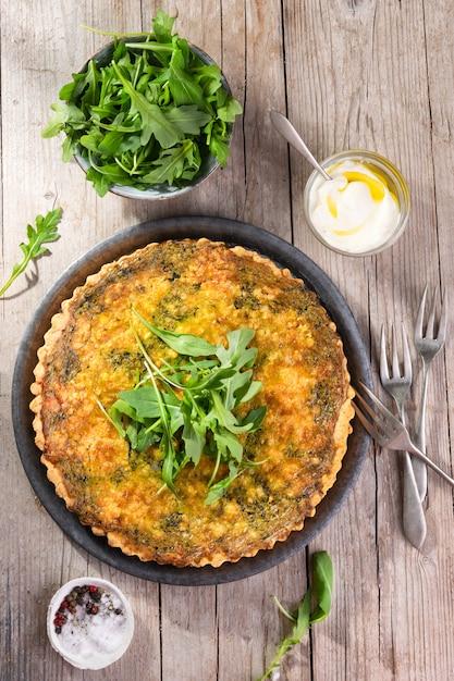 Quiche com rúcula, cebola, espinafre, mussarela, queijo feta e molho Foto Premium