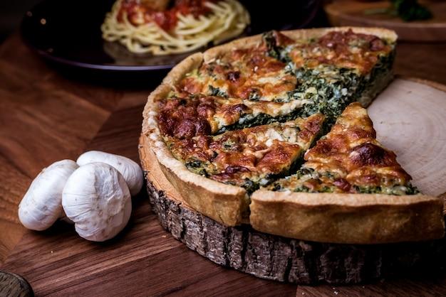 Quiche uma torta aberta saborosa com espinafre cogumelos queijo. Foto Premium