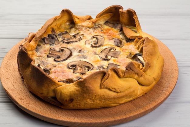 Quishe com cogumelos em uma placa de madeira Foto Premium