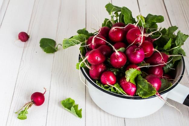 Rabanetes vermelhos na tigela na mesa de madeira Foto gratuita