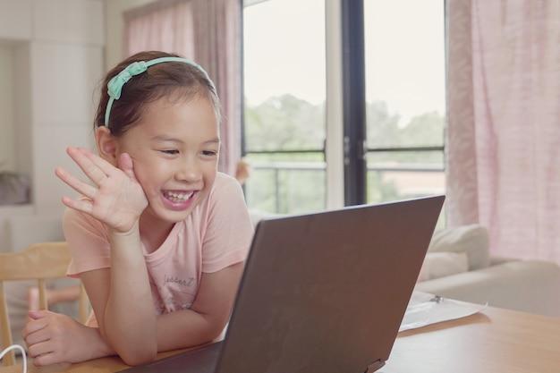 Raça mista jovem menina asiática fazendo chamada de vídeo facetime com laptop em casa, usando o aplicativo de aprendizagem on-line zoom, distanciamento social, isolamento, educação em casa, aprendendo remotamente o conceito Foto Premium