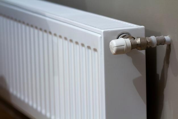 Radiador de aquecimento branco com válvula termostato na parede no interior de um apartamento após obras de renovação. Foto Premium
