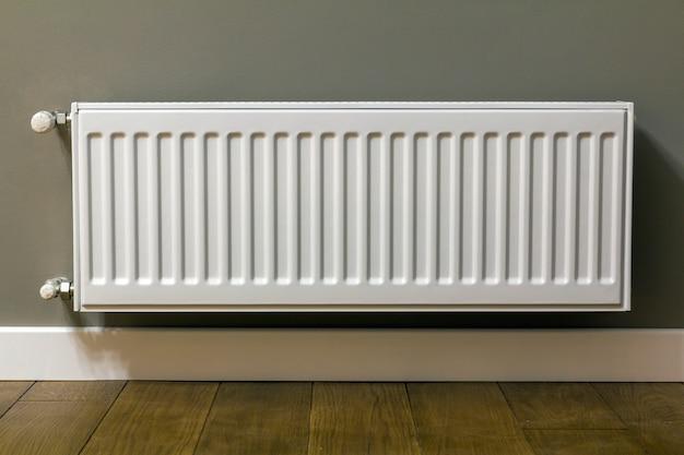 Radiador de aquecimento branco na parede de um apartamento com piso de madeira Foto Premium