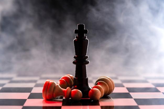 Rainha do xadrez derrota um lote de peões brancos em um tabuleiro de xadrez em um fundo com fumaça Foto Premium