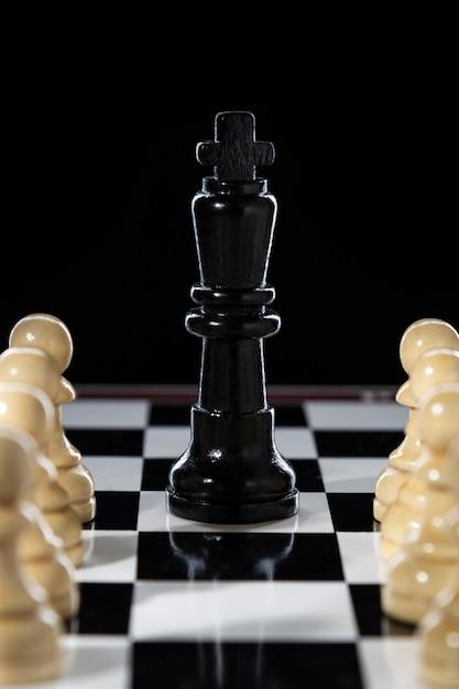 Rainha do xadrez preto e exército de peões brancos em um tabuleiro de xadrez Foto Premium