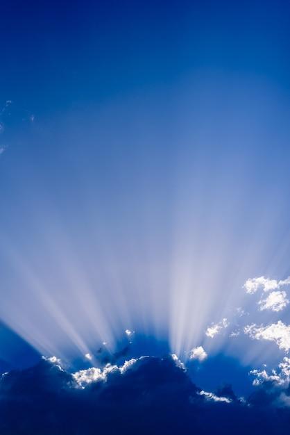 Raios solares subindo de uma grande nuvem no céu azul intenso em uma tarde de verão Foto Premium