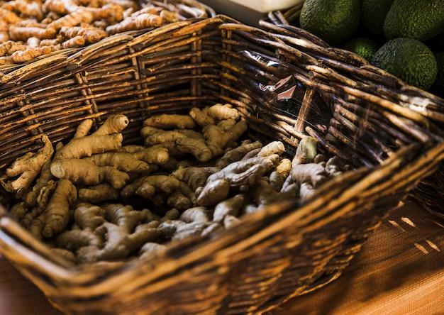 Raízes de gengibre frescas na cesta de vime marrom no mercado mercearia Foto gratuita