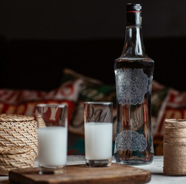 Raki de vodka turca em copos com uma garrafa de lado. Foto gratuita