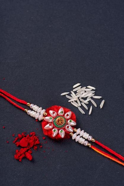 Raksha bandhan: rakhi com grãos de arroz e kumkum, pulseira indiana tradicional que é um símbolo de amor entre irmãos e irmãs. Foto Premium