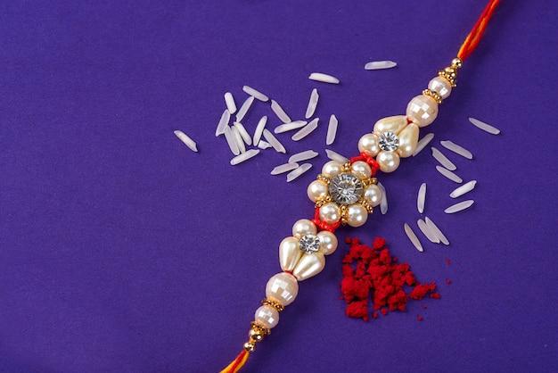 Raksha bandhan: rakhi com grãos de arroz e kumkum. um festivo indiano. pulseira indiana tradicional, que é um símbolo de amor entre irmãos e irmãs. Foto Premium