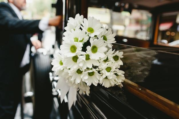 Ramalhete das margaridas que decoram um carro antigo do casamento. Foto Premium