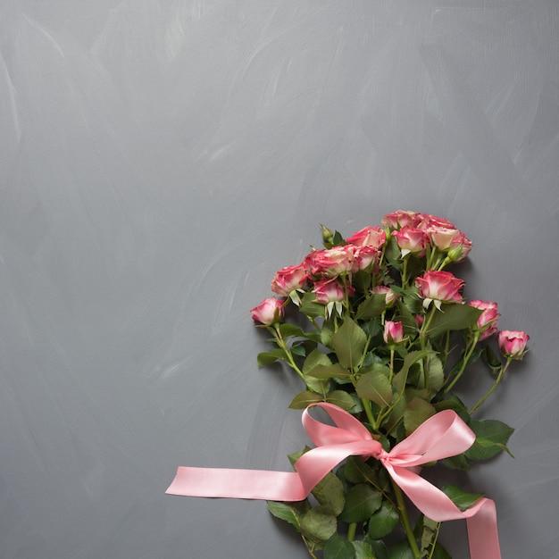 Ramalhete de rosas cor-de-rosa do arbusto com curva cor-de-rosa no cinza do vintage. Foto Premium