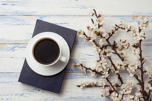 Raminho de cerejas com flores e copo branco com café preto e um livro sobre um fundo branco de madeira. Foto Premium
