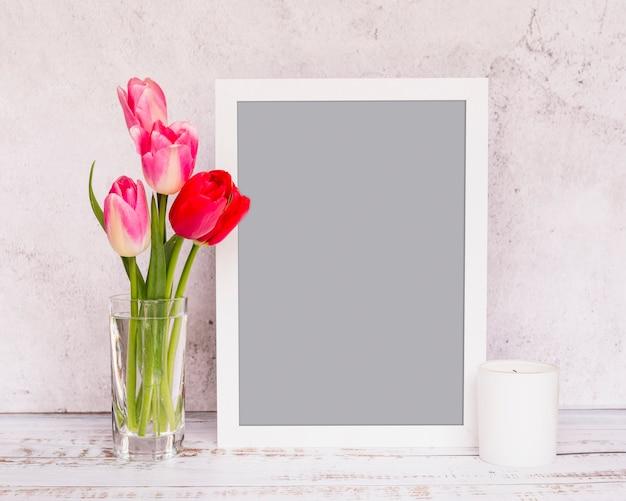 Ramo de flores frescas em caules em vaso perto de quadro e vela Foto gratuita