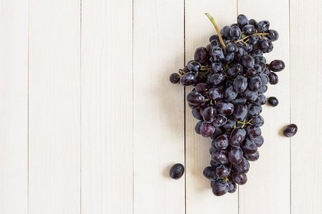 Ramo de uva preta em madeira branca Foto gratuita