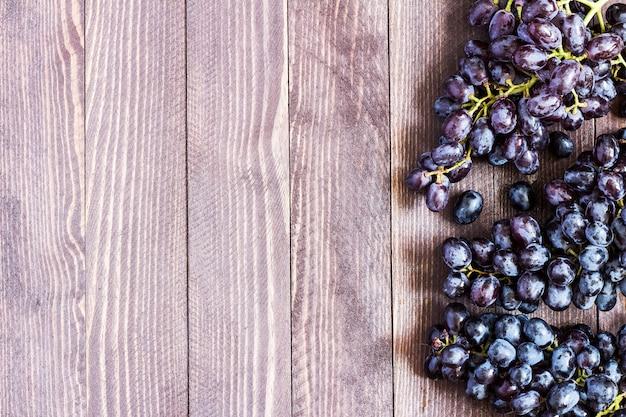Ramo de uva preta em madeira escura Foto gratuita