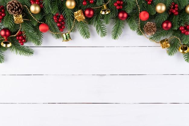Ramos de abeto de natal, pinhas, bagas vermelhas em fundo de madeira. Foto Premium