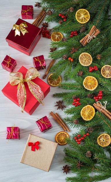 Ramos de abeto, decoração, frutas, fatias de laranja, canela e presentes de diferentes formas Foto Premium