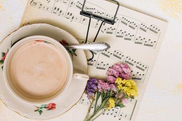 Ramos de pequenas flores com uma xícara de café na partitura Foto gratuita