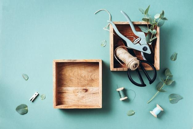Ramos e folhas de eucalipto, podador de jardim, tesoura, caixas de madeira Foto Premium
