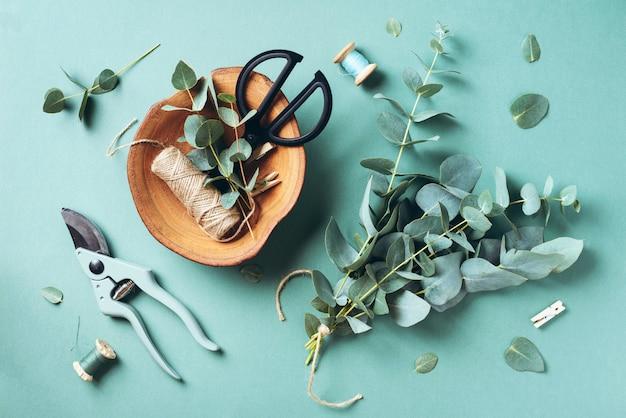 Ramos e folhas de eucalipto, podador de jardim, tesoura, placa de madeira Foto Premium