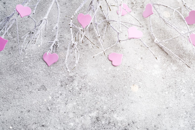 Ramos na neve com corações rosa em um fundo de concreto Foto Premium