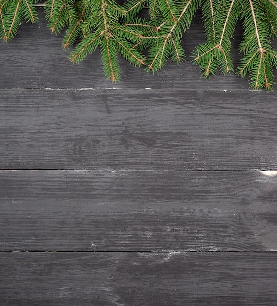 Ramos verdes de uma árvore de natal em um fundo preto de madeira Foto Premium