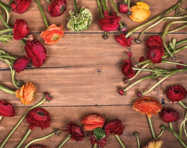 Ranunkulyus buquê de flores vermelhas em uma mesa de madeira Foto gratuita