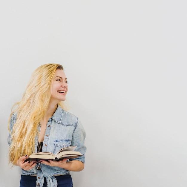 Rapariga com livro rindo Foto gratuita