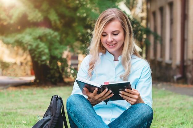 Rapariga estudante senta-se na grama, lê um livro e sorri em um parque em um fundo de universidade Foto Premium