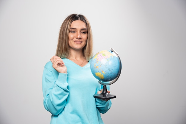 Rapariga loira com moletom azul segurando um globo, adivinhando a localização e se divertindo Foto gratuita