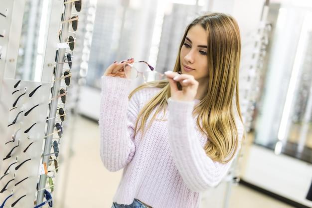 Rapariga loira com suéter branco escolhe novos óculos médicos em loja profissional Foto gratuita