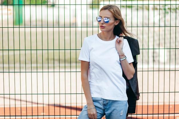 Rapariga loira vestindo camiseta, óculos e jaqueta de couro posando contra a rua Foto Premium