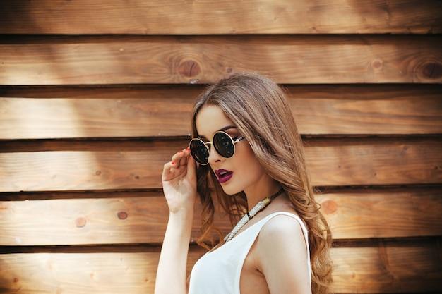 Rapariga no t-shirt branco posando com fundo de madeira Foto gratuita