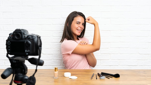 Rapariga que grava um tutorial em vídeo, fazendo um gesto forte Foto Premium