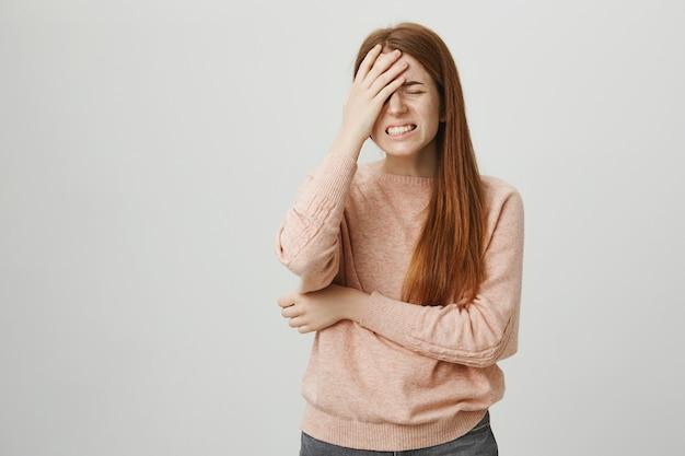 Rapariga ruiva angustiada na palma da mão, sentindo-se frustrada Foto gratuita