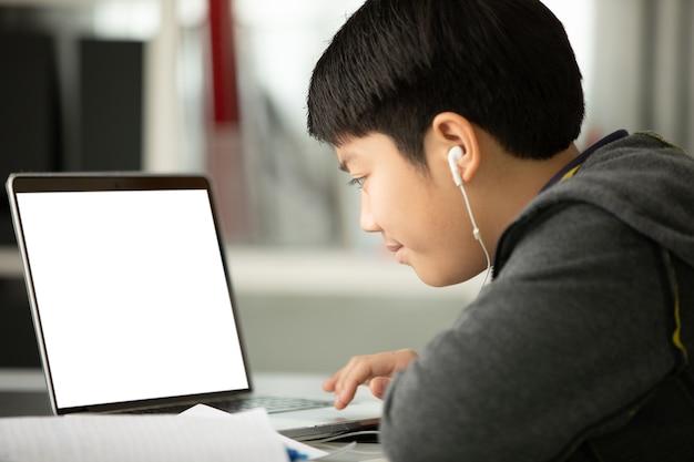 Rapaz adolescente asiático usando computador portátil em casa, Foto Premium