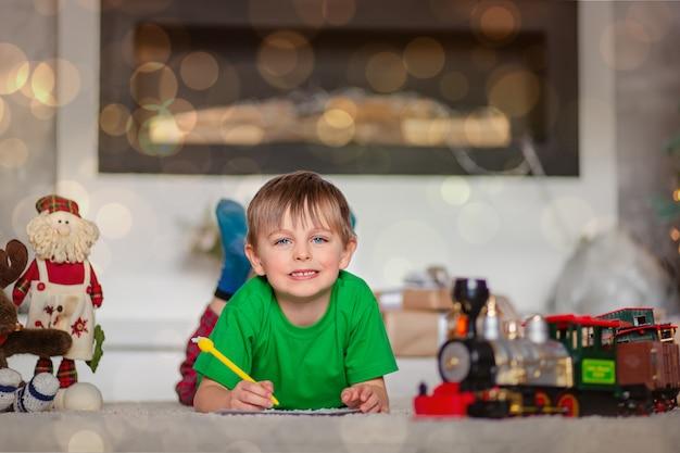 Rapaz alegre é uma carta para o papai noel, perto da árvore de natal. infância feliz, tempo para realizar desejos. Foto Premium