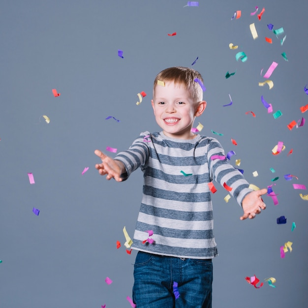 Rapaz alegre pegando confete Foto gratuita