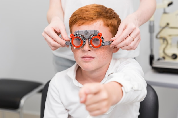Rapaz, apontando para a câmera enquanto oftalmologista feminina examinar seus olhos Foto gratuita